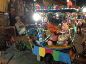 At Mengwi night markets, a charming carousel for babies, powered by an old man pedalling